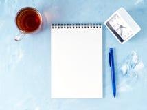 Odgórny widok nowożytny jaskrawy błękitny biurowy desktop z notepad, zegar, kwiatu sukulent Egzamin próbny up, opróżnia przestrze Zdjęcie Stock