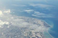 Odgórny widok od desantowego samolotu Okno samolot z kopii przestrzenią Widok z lotu ptaka chmury, morza, oceanu i miasta krajobr Fotografia Royalty Free