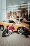 Odgórny widok ojciec i syn słucha konsultant mówi o samochodzie obraz stock