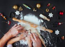 Odgórny widok ojcowie i dzieciaki wręcza robić Bożenarodzeniowym ciastkom na b fotografia royalty free