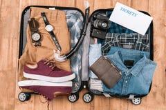 Odgórny widok otwarty bagaż mężczyzna pełno odziewa, gadżety i inne istotne urlopowe rzeczy, obraz royalty free