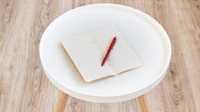Odgórny widok otwarty pusty pusty nutowy papier z czerwonym piórem na białym round czasopisma drewna stole dla tła fotografia royalty free