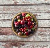 Odgórny widok Owoc i jagody w pucharze na drewnianym tle Dojrzali rodzynki, malinki, wiśnie, truskawki, agresty, czarni Fotografia Stock
