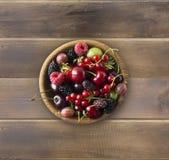 Odgórny widok Owoc i jagody w pucharze na drewnianym tle Dojrzali rodzynki, malinki, wiśnie, truskawki, agresty, czarni Zdjęcia Royalty Free