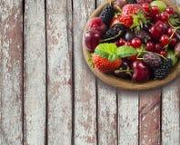 Odgórny widok Owoc i jagody w pucharze na drewnianym tle Dojrzali rodzynki, malinki, wiśnie, truskawki, agresty, czarni obrazy stock