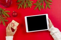 Odgórny widok pastylka komputer w kobiet rękach Bożenarodzeniowe dekoraci i jodły gałąź na czerwonym tle zdjęcia stock