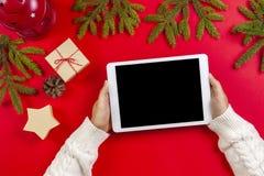 Odgórny widok pastylka komputer w kobiet rękach Bożenarodzeniowe dekoraci i jodły gałąź na czerwonym tle obraz royalty free