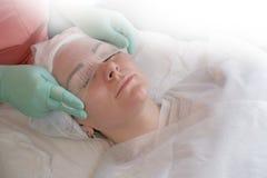 Odgórny widok piękna kobieta która bierze piękno traktowania przy zdrojem Cosmetologist pokryw gazy twarzy żeński zbliżenie obraz royalty free