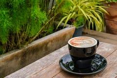 Odgórny widok pięknie dekorująca latte kawa w czarnym cera obrazy stock