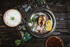 Odgórny widok piec łososiowy stek z cytryną na nieociosanej metal tacy z ryżowym bocznym naczyniem fotografia stock