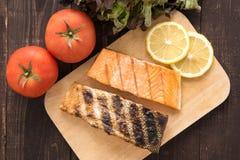 Odgórny widok piec na grillu łososia na tnącej desce na drewnianym tle Zdjęcia Stock