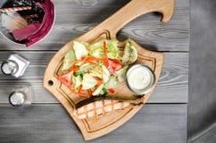 Odgórny widok Piec na grillu łososiowego stek z winnika kumberlandem i świezi warzywa słuzyć na drewnianym stole przy restauracją Fotografia Stock