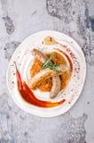 Odgórny widok Piec na grillu kiełbasy z stewed kapustą z pieprzowego kumberlandu ketchupem, chili, musztarda na białym talerzu na Obrazy Stock