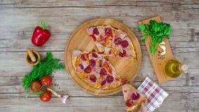 Odgórny widok pizza ciie od drewnianego talerza na stole zatrzymuje ruch animację, 4K