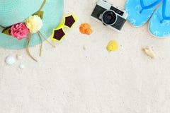 Odgórny widok plażowy piasek z słomianym kapeluszem, okularami przeciwsłonecznymi, skorupami, kamerą, kapciami i koralem, Obraz Stock