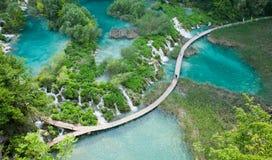 Odgórny widok Plitvice jeziora z siklawami i drewnianymi przejściami z turystą Zdjęcie Royalty Free