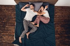 Odgórny widok Podrażnionych krzyczących kobiet pchnięć przystojny chrapa mężczyzna z łóżka obrazy stock