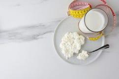 Odgórny widok posiłków składniki dla milky diety, strata ciężar Łyżka z chałupa serem i talerzem, szkło z milky produktem, pomiar obrazy royalty free