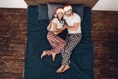 Odgórny widok Potomstwa dobierają się w Święty Mikołaj kapeluszy kłamstwach na łóżku, obejmuje each inny zdjęcie royalty free