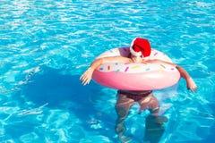 Odgórny widok potomstwo pijący facet w bożego narodzenia kapeluszowym pływaniu z menchia okręgiem w basenie opiły facet na wakacj obraz royalty free