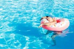 Odgórny widok potomstwo pijący faceta pływanie z menchia okręgiem w basenie opiły facet na wakacje w hotelu fotografia stock