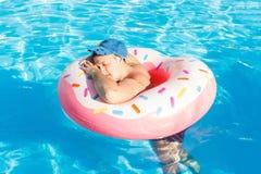Odgórny widok potomstwo pijący faceta pływanie z menchia okręgiem w basenie opiły facet na wakacje w hotelu obrazy royalty free