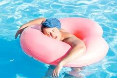 Odgórny widok potomstwo pijący faceta pływanie z menchia okręgiem w basenie opiły facet na wakacje w hotelu fotografia royalty free