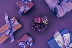 Odgórny widok prezentów pudełka z fiołkowymi faborkami i pięknymi kwiatami Zdjęcia Stock