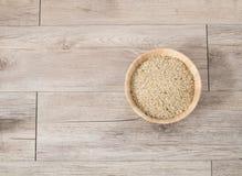Odgórny widok - Prostacki ryż na drewnianym talerzu na drewnianym tle i zdjęcie stock