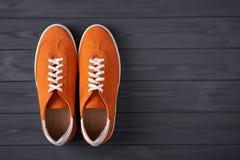 Odg?rny widok przypadkowi pomara?czowi zamszowy trenery na popielatych drewnianych deskach fotografia stock