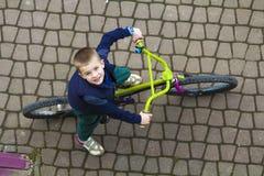 Odgórny widok przystojna młoda uśmiechnięta chłopiec jedzie bicykl na chłodno wiosna dniu patrzeje oddolny Outdoors aktywność zdr zdjęcie royalty free