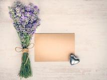 Odgórny widok pusta powitania Kraft karta, lawendowy bukiet i srebra serce nad białym drewnianym nieociosanym drewnianym stołem,  Obraz Royalty Free