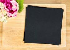 Odgórny widok Pusty drewniany talerz z czerń papierem i kwiatu garnkiem na stole Zdjęcie Stock