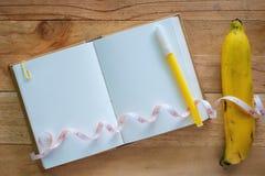 Odgórny widok pusty dzienniczka notatnik, żółty pióro, banan i miara taśmy na drewnianym stole, fotografia stock