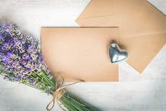 Odgórny widok pusty powitania Kraft envlope, karta, lawendowy bukiet i srebra serce nad białym drewnianym nieociosanym drewnianym Fotografia Stock