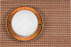 Odgórny widok pusty styl malujący wschodu teacup na spodeczku lokalizować na drewnianej bambus macie Obraz Royalty Free