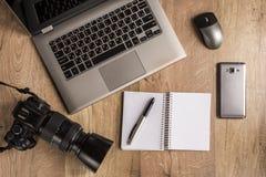 Odgórny widok różni gadżety i przyrząda na stole: komputer osobisty, komputer, pióro, nutowa książka, klawiatura, ołówek, notatni fotografia royalty free