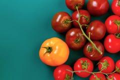 Odgórny widok różnorodna czerwień, kolor żółty, czarni pomidory, isolaetd na zielonym ciemnym tle obraz royalty free