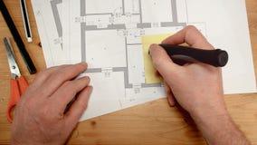 Odgórny widok ręka projektant wnętrz atakuje żółtą pocztę na technicznym rysunku nowy dom i pisze do domu zbiory wideo