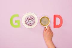 Odgórny widok robić od dobre słowo i filiżanka kawy w ludzkiej ręce i donuts Obrazy Stock