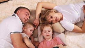 Odgórny widok rodzina która jest odpoczynkowa na koc, poduszkach i oglądać jej córki bawić się pastylkę, zbiory wideo