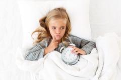 Odgórny widok rozważny małej dziewczynki lying on the beach w łóżku z budzikiem Fotografia Stock