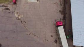 Odgórny widok ruszać się dużą czerwieni ciężarówkę z długą popielatą przyczepą przy budowa terenem zdjęcie wideo