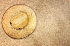 Odgórny widok słomiany kapelusz na plażowym piasku Obrazy Royalty Free