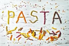 Odgórny widok słowo makaron, pisać w barwiącym fusilli robić pszeniczna pasta, na białym drewnianym tle Obraz Stock