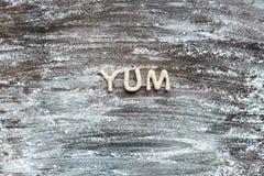 Odgórny widok słowo yum zrobił od ciastka ciasta z mąką obraz stock