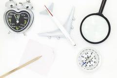 Odgórny widok samolotu model, budzik, kompas, Powiększający - szkło i białej księgi notatka na białym tle zdjęcie stock