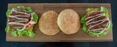 Odgórny widok, składniki hamburgery umieszczający na drewnianej tnącej desce fotografia royalty free