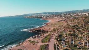 Odgórny widok skalisty seashore koral zatoka w ciborze z palmami, hotelami i kurortu terenem, Silny morze macha uderzający skalis zdjęcie wideo