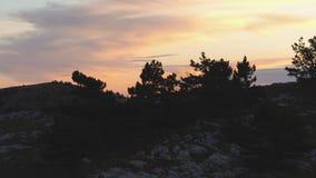 Odgórny widok skalisty wierzchołek na tle zmierzch barwi z chmurami strzał Kolorowy malowniczy krajobraz zmierzchu niebo zdjęcie wideo